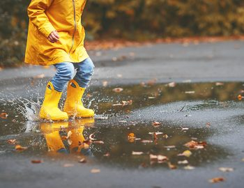 Legs of a child wearing yellow gumboots splashing in a puddle in autumn
