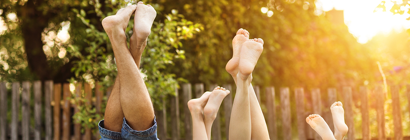 A family with their legs and feet being held up in the air, with the sun shining