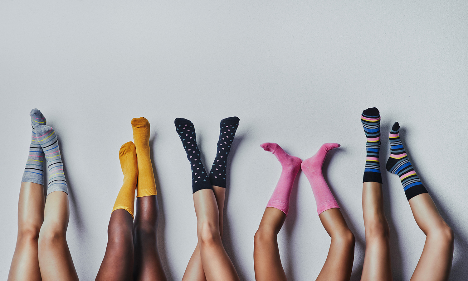 five pairs of legs against a wall, wearing coloured and patterned socks
